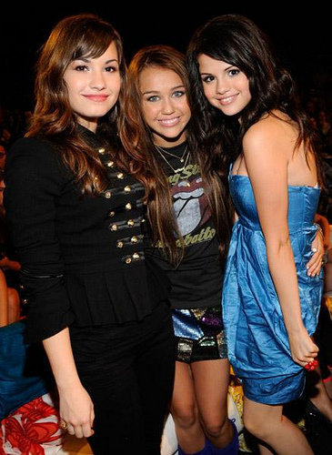 Miley Cyrus vs. Selena Gomez দেওয়ালপত্র possibly with a hip boot titled বন্ধু together