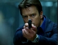 Nathan /Castle with a gun and a Ball Watch on his wrist.