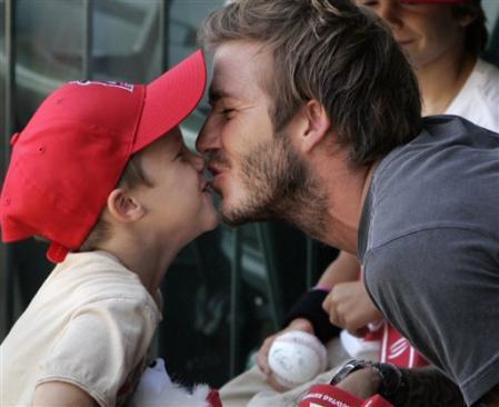 Soccer star David Beckham gets a kiss from son Cruz during a baseball game