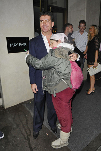 Simon Cowell kisses a fan on the cheek