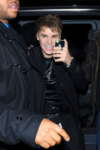 Justin Bieber takes a snap on his IPhone as he stops at La Portes Des Indes restaurant in London