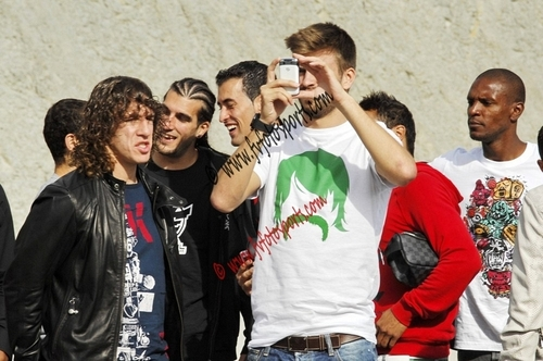 Pique takes a picture of his new car talking with Puyol.