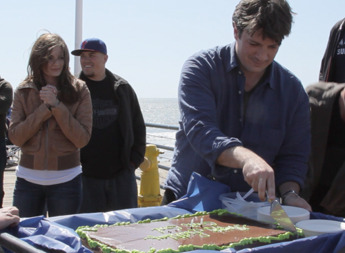 Nathan cutting his birthday's cake and Stana watching behind.