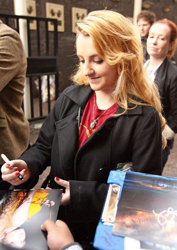 Evanna Lynch achtergrond containing a sign and a newspaper titled Signing Autographs Outside ITV Studios April 11th, 2011