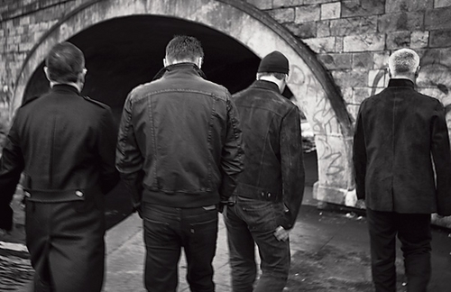 U2 wallpaper with a street, a portcullis, and a business suit titled Backs to Black