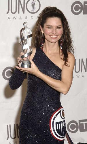 Shania Twain karatasi la kupamba ukuta possibly with a sign, a cocktail dress, and a bouquet titled Juno muziki Awards 2003
