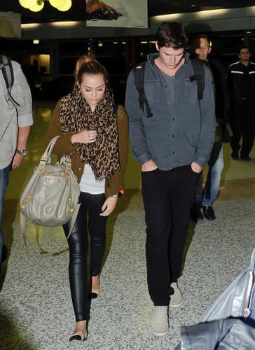 Miley Cyrus is all smiles as she arrives in Brisbane, Australia with boyfriend Liam Hemsworth.