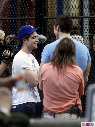 Robert Pattinson on the set of Cosmopolis (with a gun)