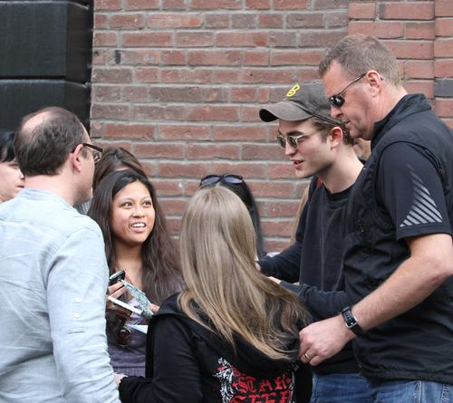 Rob signing autograph to fans at cosmpolis set