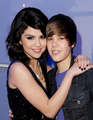 Selena with her arms around Justin