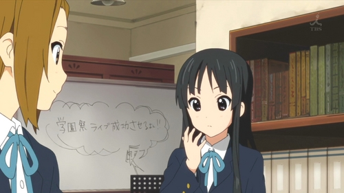 (S2)In EP20 HTT play a prank on Mio by writing 'person' a lot on her hand. She then psyches for the concert with a ritual related to this. What is this, and what for?