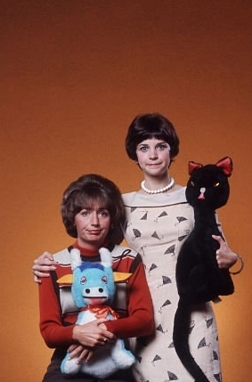 What is the name of the stuff toy cat that Shirley is holding in the picture?