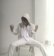During part of the video for 'Cloud', Jui sits singing on a white chair as who appears directly in front of him?