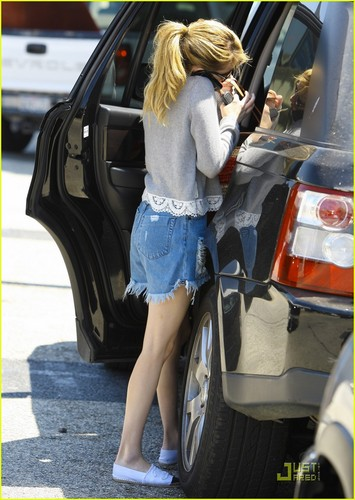Emma Roberts cradles her cell phone on her neck as she arrives at the Ken Paves Salon on Friday